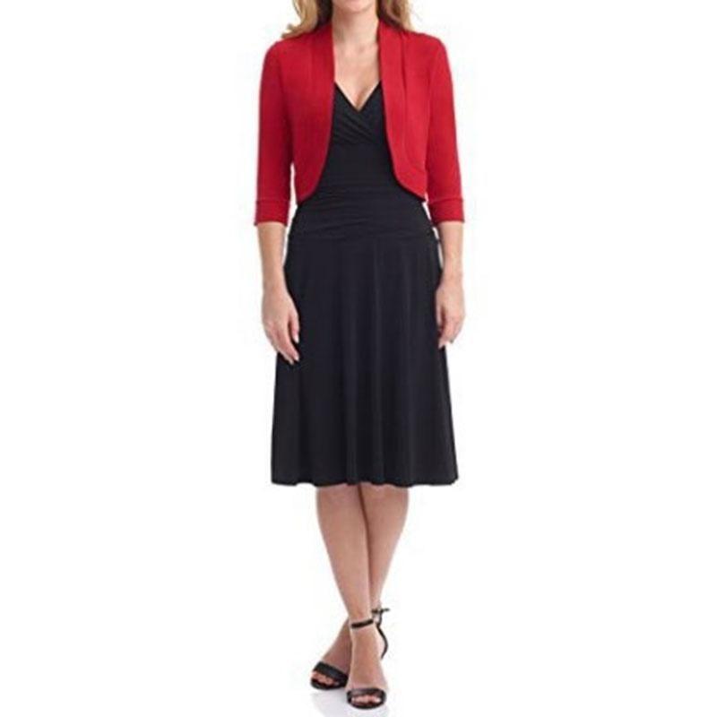 mujer con vestido negro con abrigo rojo