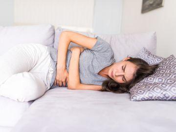 mujer acostada con dolor de estómago