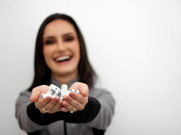 mujer sonriente con suplementos en mano