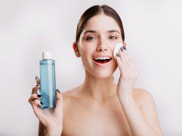 Mujer limpiando su rostro con tónico
