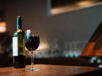 botella y copa de vino tinto sobre la mesa