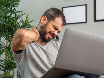 hombre frente a la computadora con dolor muscular