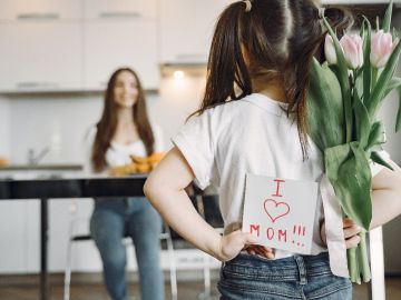 niña de espaldas con letrero de I Love Mom