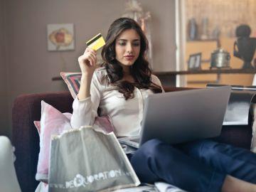 mujer con laptop y tarjeta de crédito
