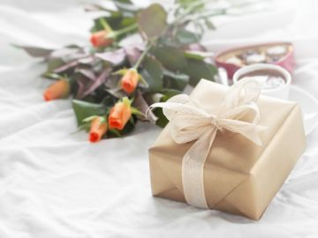 flores y regalo sobre la cama