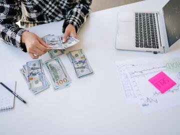 mujer contando billetes de 100 dólares