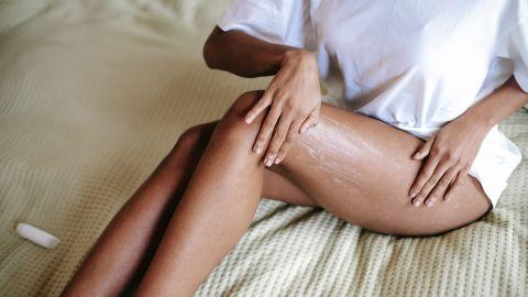 mujer con crema en las piernas