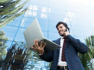 hombre con laptop y celular