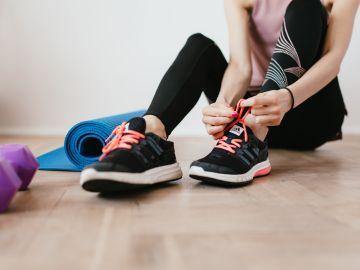 mujer atando los cordones de los zapatos
