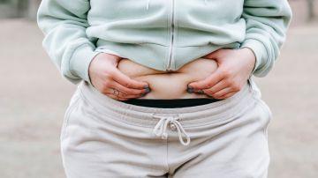 Mujer agarrándose el abdomen