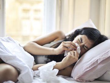 mujer acostada con resfriado